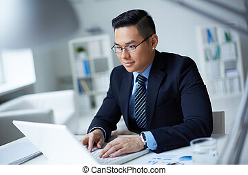Businessman typing - Smiling businessman in suit typing on...