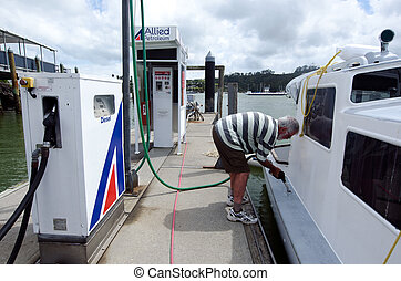 Man fuels his boat - BAY OF ISLANDS, NZ - DEC 12:Man fuels...