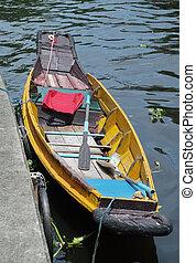 Row boat moored at the riverbank