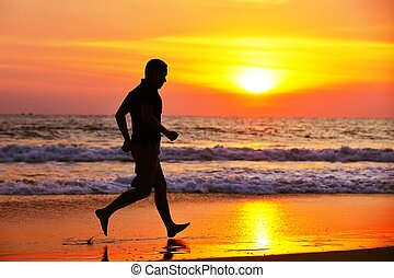 Running - Young man is running on the beach at sunset.