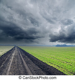 road in green fields to low rainy clouds