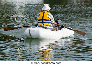 Man rows dinghy boat - Man rows a rubber inflatable dinghy...
