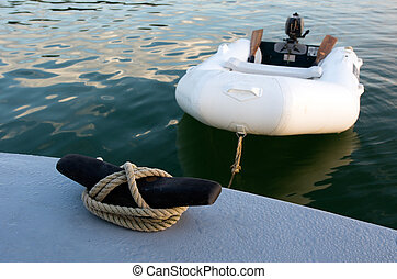 Rubber inflatable dinghy boat towed to a boat.