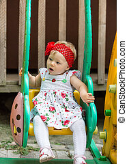 year-old adorable little child girl sitting on a swing at...