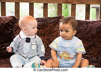 Small two children: black american and caucasian boys siting...