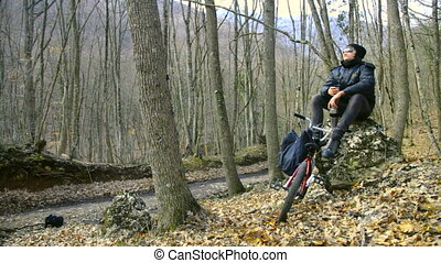 A teenager on a bicycle in the autumn forest
