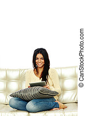 Young smiling woman sitting on the sofa with tablet computer and looking at camera