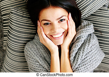 Portrait of a young smiling woman lying on the floor with...