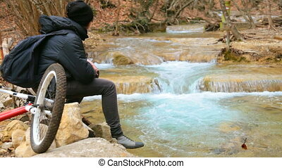 Teen boy with bike resting in woods by river - Teenager with...