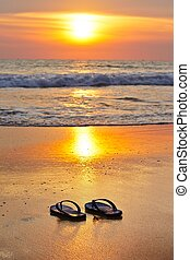 Flip flops on the beach at sunset