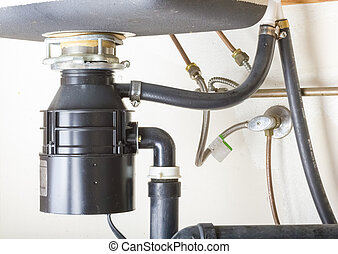 Under the sink. - Under the sink garbage disposal unit.