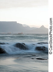 Water on rocks - Rocks and waves with Table Mountain in the...
