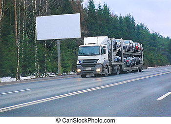 truck transports car against winter forest