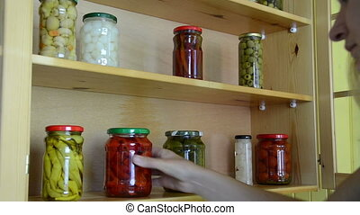 pickled pepper tomato jar - woman puts jars with pickled red...