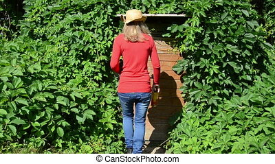 woman cellar outside - countrywoman with a straw hat came...