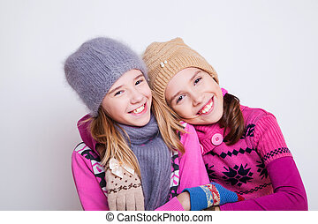 Portrait of two young beautiful girls on the white...