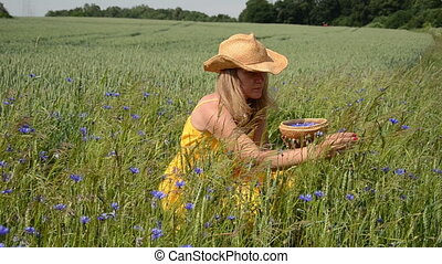 girl gather herb blooms - Pretty farm girl in dress and hat...