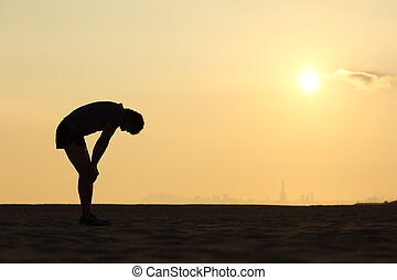 Silhouette of an exhausted sportsman at sunset with the...