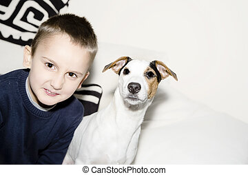 Young boy with his dog sitting on couch