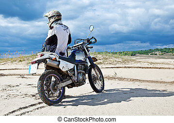 Enduro bike rider driving across the desert