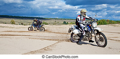 Enduro bike riders driving through the desert