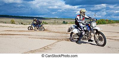 Enduro bike riders driving through the desert