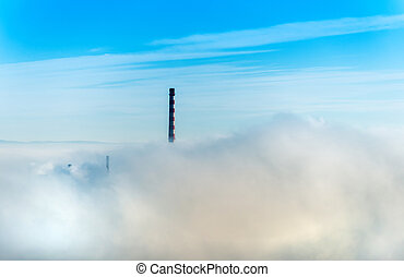 Factory chimneys and clouds of steam.Blue sky