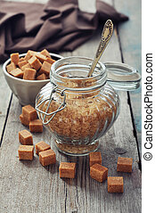 Brown candy sugar in glass jar on wooden background