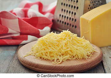 Grated cheese on wooden cutting board closeup