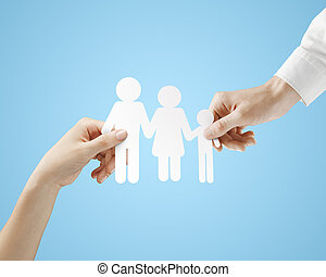 paper family - hands holding paper family on a blue...