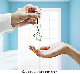 key in hands - passing key against backdrop of blue room