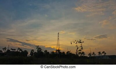 High voltage electric pylons at sunset with timelapse clouds...