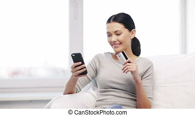 smiling woman with smartphone and credit card