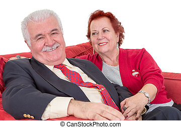 Devoted senior couple seated on a red sofa