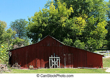 Old red barn with white gate on farm