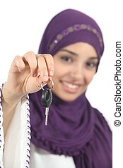 Arab woman holding and showing a car key isolated on a white...