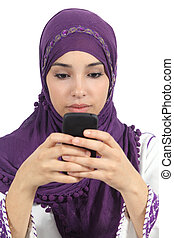 Arab woman writing a message addicted to the smart phone...