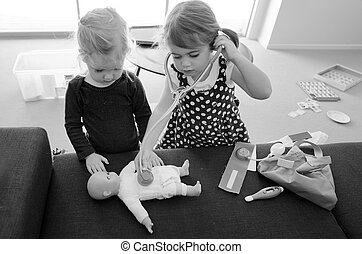 Children play doctor - Two children girls play doctor,...