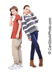two smiling teenager, back on back with their mobile phones, isolated on white.