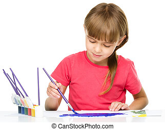 Little girl is painting with gouache while sitting at table,...