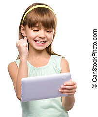 Young girl is playing game using tablet, isolated over white