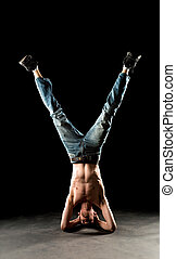 Yoga Inversion - A young white Caucasian male stands on his...