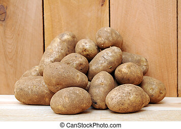 russet potatoes - a pile of russet potatoes on wooden shelf...