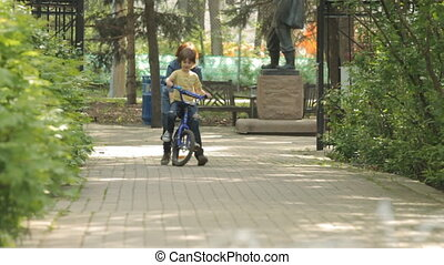 Mom Teaching Child to Ride a Bike. Slow motion