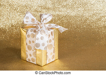 Golden gift wrapped present with dotted bow over glittery...