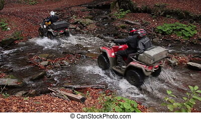quadbikes crossing river - group of people on quadrocycles...