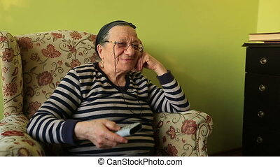 watching television - elderly woman watching television at...