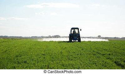 tractor fertilize field - Tractor spray fertilize field with...
