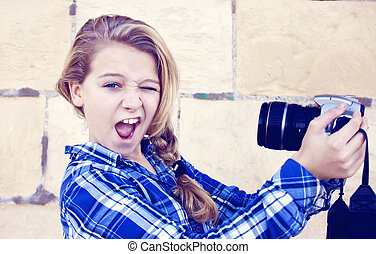 Girl holding camera - Young teenage girl doing a funny face...