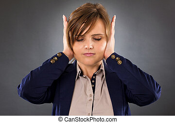 Closeup portrait of a young businesswoman covering ears with...
